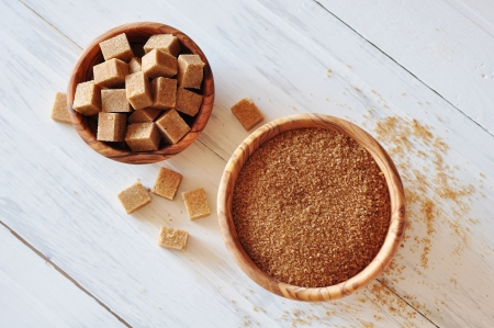sweetening: Brown sugar in wooden bowl on white wooden background