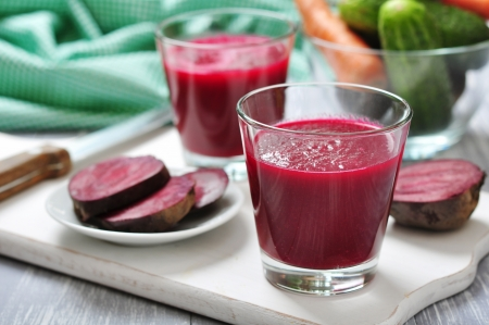Beetroot juice in glass on  wooden cutting board photo
