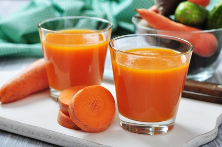 carrot juice: glasses of carrot juice and fresh carrots on wooden cutting board Stock Photo