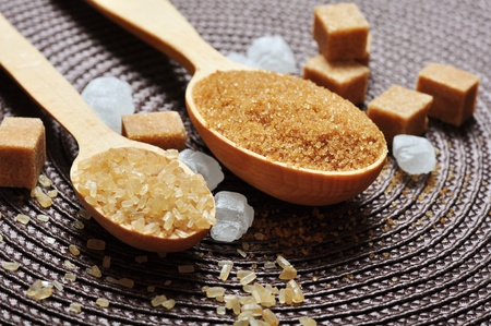 brown and white sugar in wooden spoon closeup photo