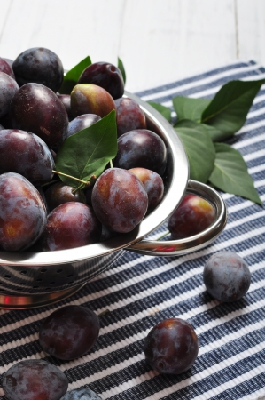 Fresh plum in metal bowl on wooden background  photo