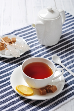 Cup with tea and teapot on blue striped background photo