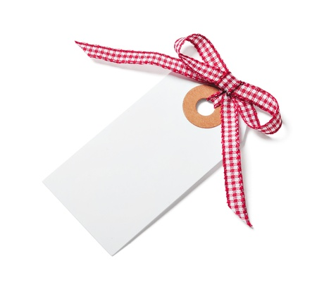 White tag with red ribbon bow isolated on white photo