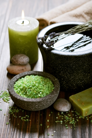 Spa concept. Sea salt in stone bowl with candle and herbal soap photo