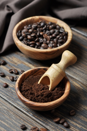 scattered: ground coffee and coffee beans in bowls on wooden background