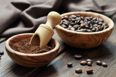 ground coffee and coffee beans in bowls on wooden background photo