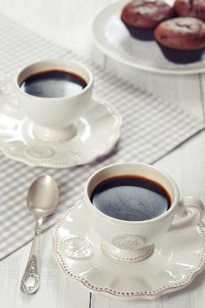cuadros blanco y negro: Taza de café con la cuchara y el chocolate magdalenas Foto de archivo