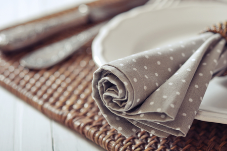 rattan mat: Fabric napkin on white plate on wicker wooden background closeup. Selective focus. Stock Photo