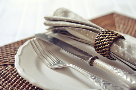 rattan mat: White plate, fork and knife on wicker wooden background closeup. Selective focus.