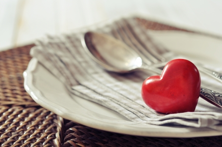 White plate, fork, knife and red stone heart on wicker wooden background closeup. Selective focus. photo