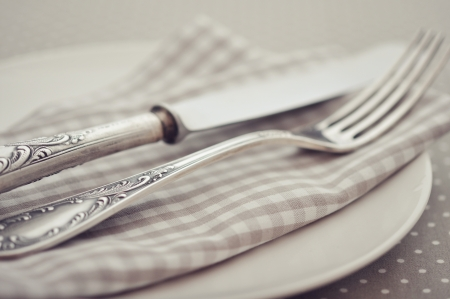 White plate, fork and knife on light polka dot background.