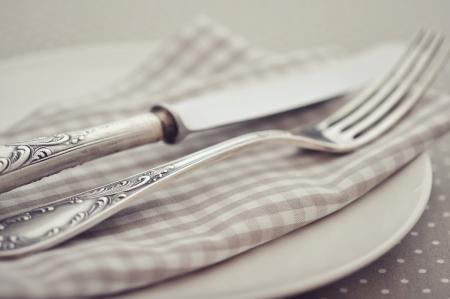 checker plate: White plate, fork and knife on light polka dot background.