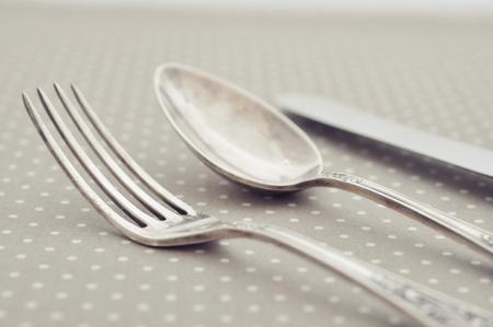 Fork, spoon and knife on light polka dot background. photo