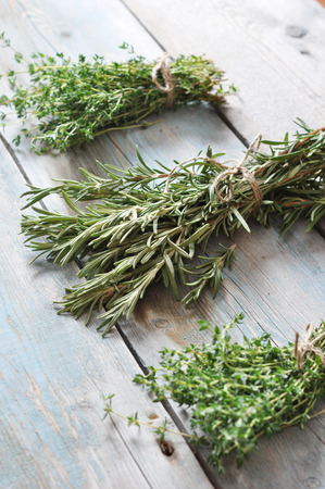 Bunchs of fresh rosemary and thyme on wooden background photo
