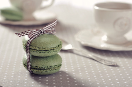 Traditional french pastry - macaroon with cup of tea on beige background photo