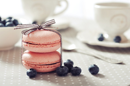 Traditional french pastry - macaroon with fresh blueberry on beige background photo