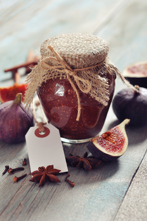 Fig jam in a glass jar with  fresh figs on wooden background photo