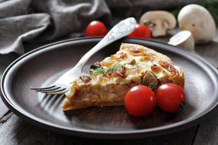 Traditional french quiche pie with chicken and mushrooms  on a wooden background  photo