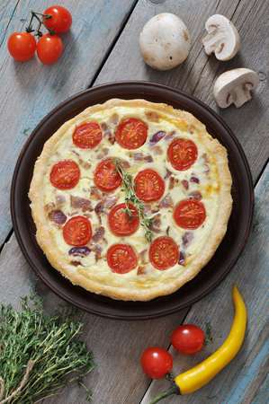 Traditional french quiche pie with chicken and cherry tomato  on a plate photo
