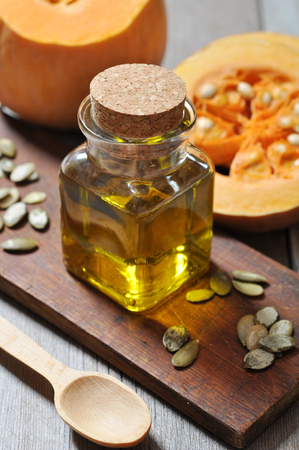 Pumpkin seed oil in glass bottle on rustic wooden background photo