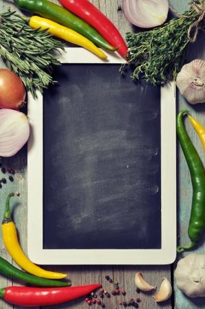 vista superior: Tarjeta de la pizarra con las verduras frescas, especias y hierbas en el fondo de madera. Vista superior.