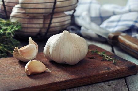 fresh garlic: Fresh garlic on cutting board on vintage wooden background Stock Photo