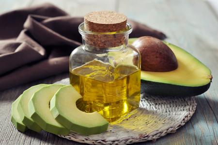 aguacate: botella de aceite esencial de aguacate con fruta fresca de aguacate primer plano