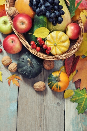 Fresh ripe pumpkins, apples, grape and nuts in wicker basket over wooden background photo