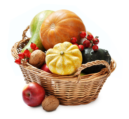 Fresh ripe pumpkins, apples, grape and nuts in wicker basket isolated on white photo