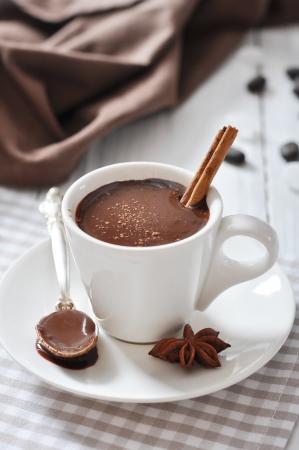 chocolate caliente: Chocolate caliente en taza con el cacao en polvo y canela en rama en el fondo de madera