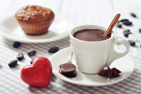 heart of stone: Hot Chocolate in cup with muffin and red stone heart on wooden background
