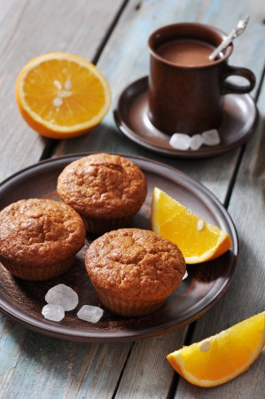 Carrot muffins with fresh oranges fruit on wooden background photo