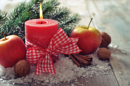 Two red candles with christmas decor on wooden background photo