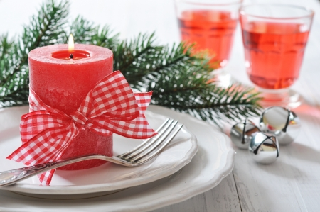 Christmas table setting with red candle and fir tree branch photo
