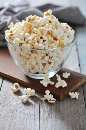 popcorn bowl: Popcorn in glass bowl over wooden background