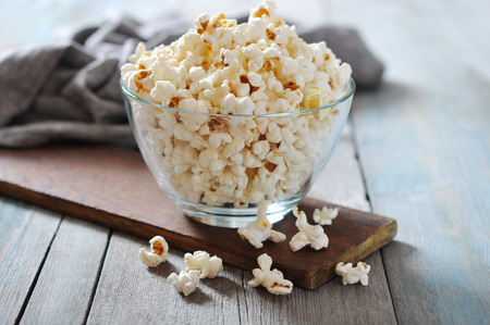 popcorn kernel: Popcorn in glass bowl over wooden background