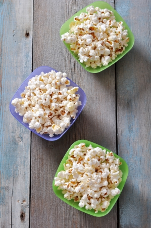 Popcorn in plastic bowls over wooden background photo