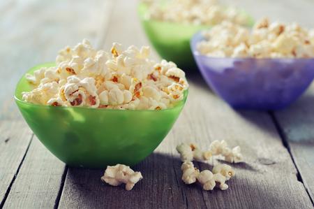popcorn bowls: Popcorn in plastic bowls over wooden background