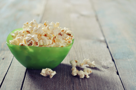 popcorn bowl: Popcorn in plastic bowl over wooden background Stock Photo