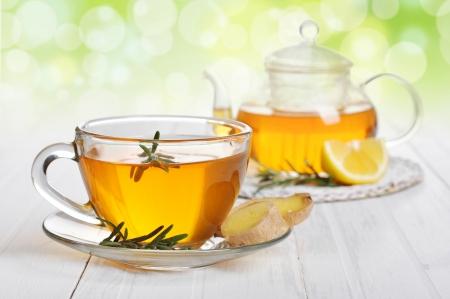 Té de jengibre con limón y rosematy en primer plano de la taza de cristal.