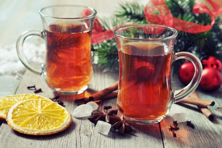 Mulled wine with spices and christmas decoration on wooden background