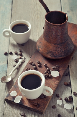 coffee pot: Coffee in cups with copper cezve on vintage wooden background Stock Photo