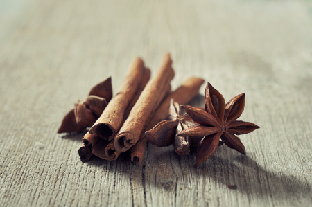 anis: Cinnamon sticks with anis stars closeup on wooden background
