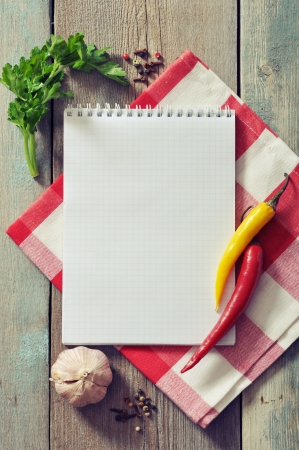 Blank recipe book with kitchen towel on wooden background photo