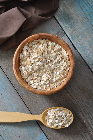 Oat flakes in wooden bowl with spoon on wooden background  photo