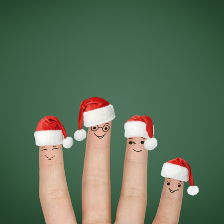 Fingers dressed in Santa hats. Happy family celebrating Christmas. photo