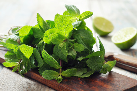 Green mint leaves with lime on wooden background
