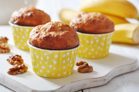 brown banana: Banana muffins in paper cupcake case with nuts over wooden background