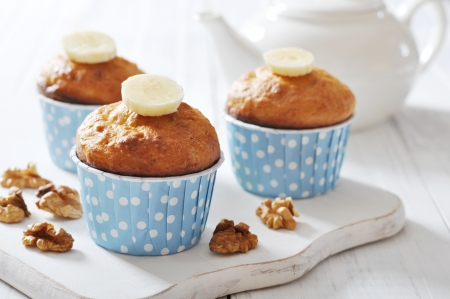brown banana: Banana muffins in blue paper cupcake case with nuts over wooden background