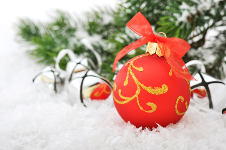 Red christmas ball and fir branches with decorations on snow photo